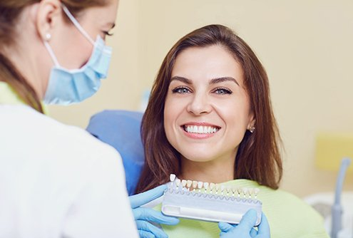 Dentist finding correct shade for patient's dental crown