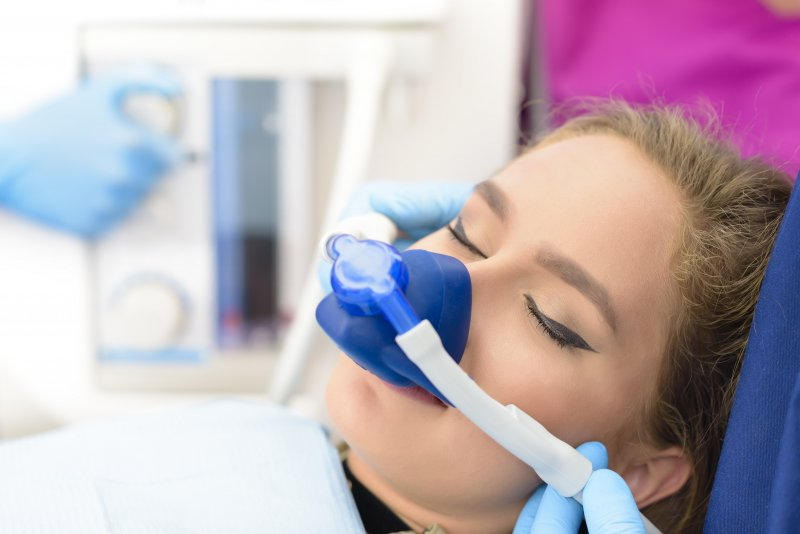 a young woman receiving nitrous oxide sedation while at the dentist's office
