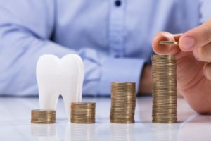 Model tooth and piles of coins demonstrate cost of dental implants in McMinnville